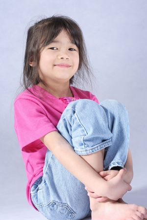 Little girl relaxed and sitting on floor Stock Photo