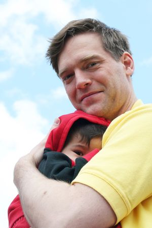 nestled: Baby boy safe and secure in his dads arms, against blue sky Stock Photo