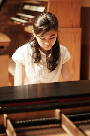 Young teen girl playing music on a grand piano photo