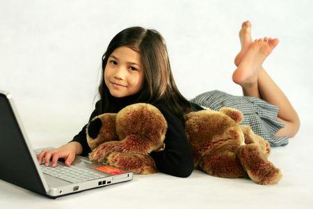 행복한 아이가 그녀의 인형 포옹하는 동안 그녀의 노트북을 즐기고 스톡 콘텐츠