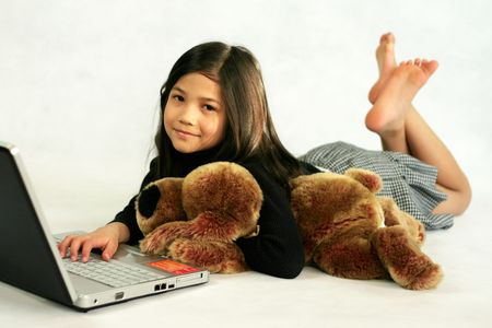 Happy child enjoying her  laptop while hugging her doll Stock Photo