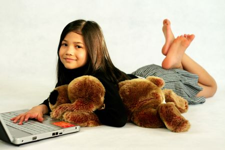 Happy child enjoying her  laptop while hugging her doll Foto de archivo