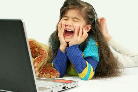 小さな女の子彼女のラップトップで再生時間について興奮しています。 写真素材