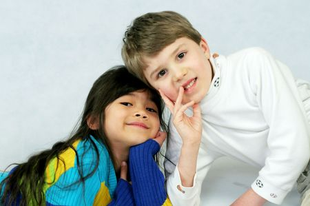 Two kids, best friends, boy and girl leaning on one another photo