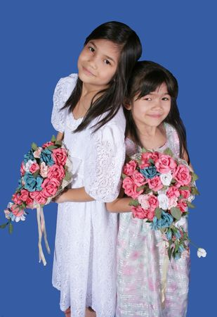 Two flower girls holding colorful floral bouquets