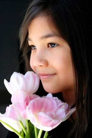 poised: Cute and poised little girl holding bouquet of pink tulips