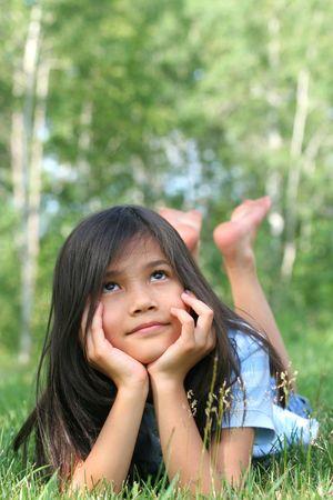 思いやりのある、空を見上げている草に横たわっている 8 歳の女の子