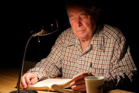 Bejaarde man lezing zijn Bijbel door de lampenlicht