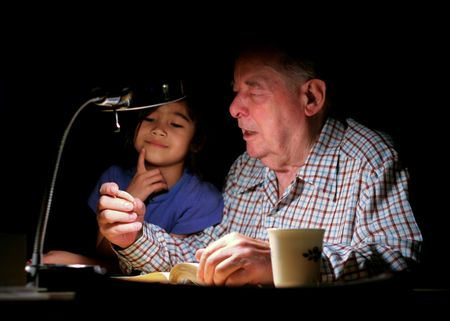 Elderly grandpa talking to great grand daughter about silver coin in hand photo