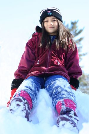 Eight years old girl siting on top of snow hill in winter in winter clothing Stock Photo