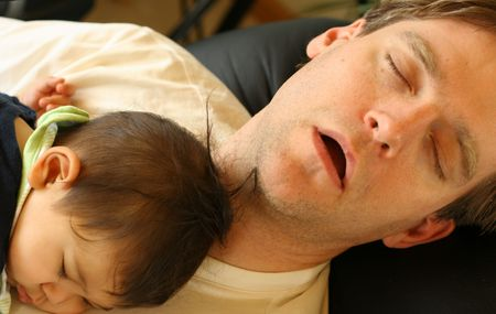 Father asleep on chair with baby boy on his chest photo