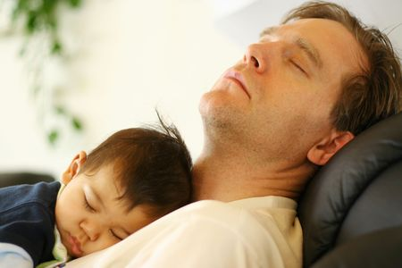 Six months old baby boy asleep on his fathers chest photo