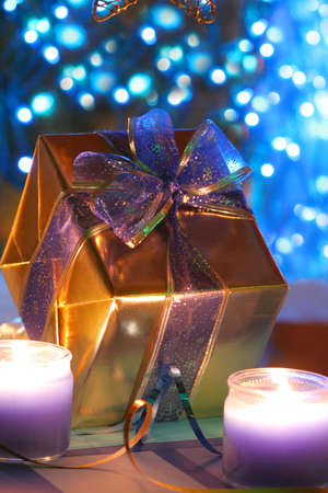 wrapped present: Gold wrapped present with bow, with blue lights in background. Stock Photo
