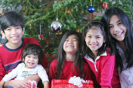 Five siblings smiling and holding Christmas presents  photo