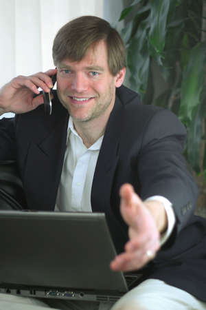 Handsome businessman on laptop and cell phone ready for handshake. photo