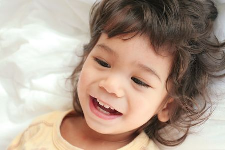 scandinavian descent: Beautiful toddler boy lying on bed laughing and smiling. Part asian, scandinavian descent. Stock Photo