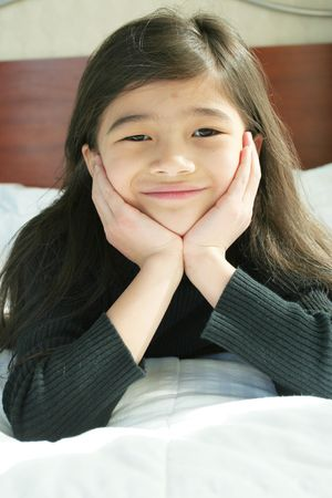 Six year old girl chin on hands thinking while lying down on bed photo
