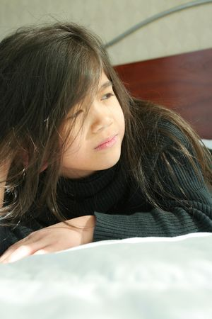 Six year old girl lying on side on bed with sad, serious expression. photo