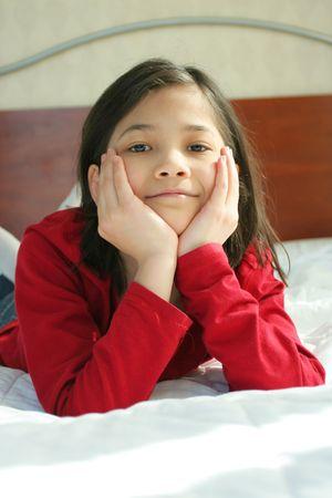 Child lying on bed thinking photo