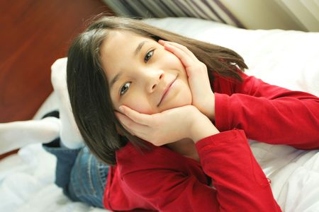 Child lying on bed thinking photo