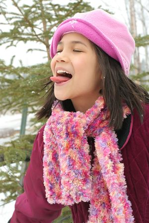 Nine year old girl sticking out her tongue trying to catch a snowflake Reklamní fotografie