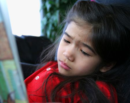 GIrl reading a story, looking sad at the sad part of story Banco de Imagens