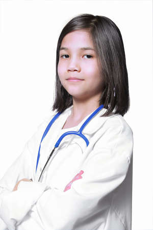 Nine year old girl playing doctor with white lab coat and stethoscope