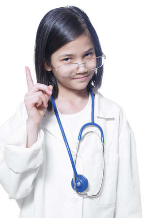sternly: Nine year old girl playing doctor with white lab coat and stethoscope lifting finger sternly Stock Photo
