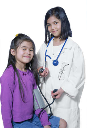 nine years old: Two girls playing doctor and patient