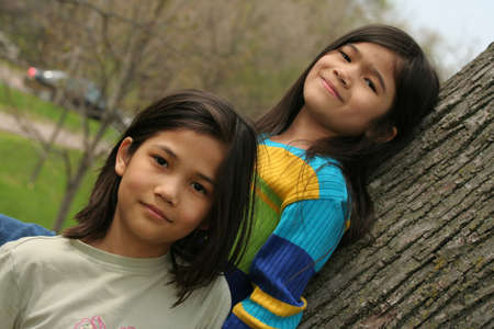 nine years old: Two little girls standing against tree in spring Stock Photo