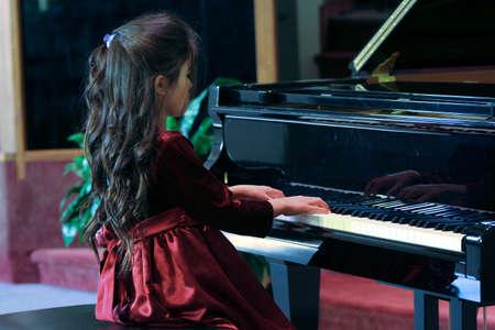 enfant qui joue: Un enfant joue piano � queue
