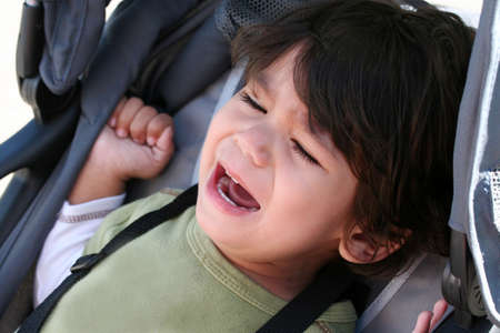 whining: Unhappy toddler crying in stroller