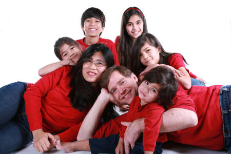 large: Large family of seven in red shirts and jeans isolated on white Stock Photo