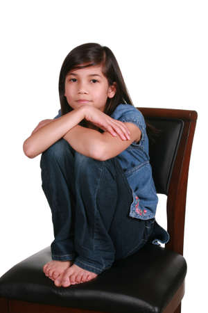 arm chairs: Little girl sitting on bar stool, somber expression. Part Asian-Scandinavian descent Stock Photo