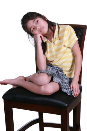 Sad seven year old sitting on chair thinking. Part Asian-Scandinavian descent. Stock Photo