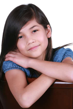 nine years old: Beautiful young girl, part asian - scandinavian descent, relaxing in chair