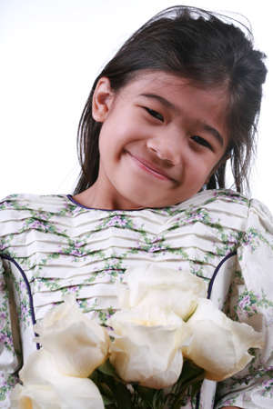 白いバラの一握りを持ってアジアの子 写真素材