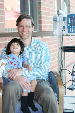 hooked up: Father holding child in hospital with IV hooked up