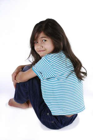 scandinavian descent: Happy little girl sitting with arms around knees, part asian - scandinavian descent