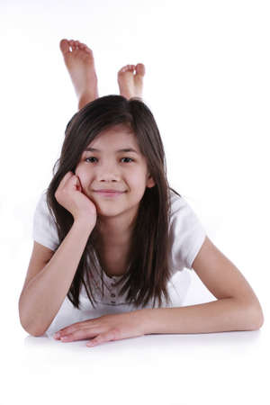 chin on hands: Beautiful ten year old girl happily relaxing on floor