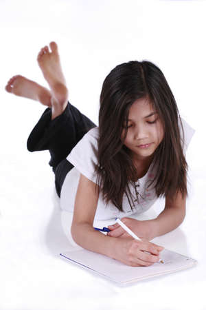 Child studying or writing while lying on floor Standard-Bild