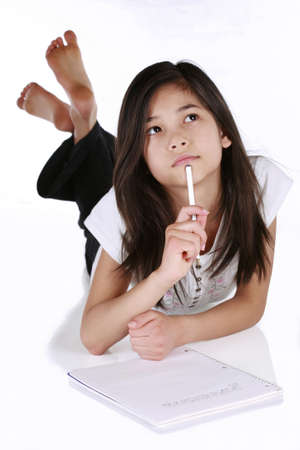 children writing: Child thinking while writing in notebook, lying on floor. Stock Photo