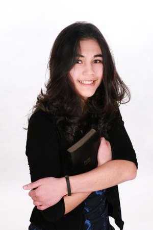 causcasian: Teen girl holding Bible, smiling