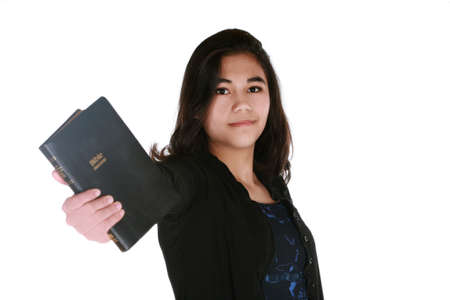 authoritative: Teen girl holding out Bible towards viewer, serious expression