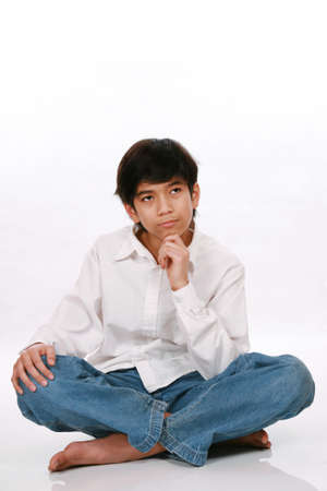 Twelve year old boy sitting, thinking with chin on hand