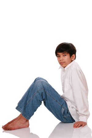 Twelve year old boy sitting on floor, with soft reflection
