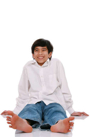 Twelve year old  boy sitting on floor, part Asian - Scandinavian descent Stock Photo