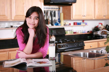 home appliances: Teen girl relaxing in kitchen with magazine and glass of milk