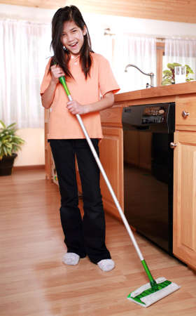 Girl happily mopping kitchen floor Stock Photo