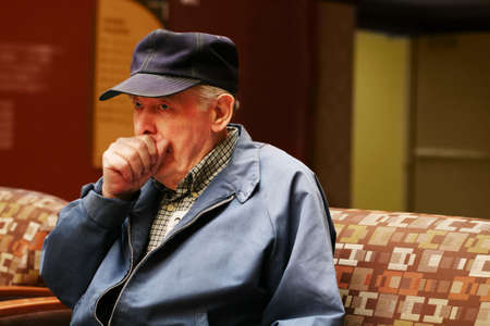 couching: Elderly man coughing in doctors waiting room